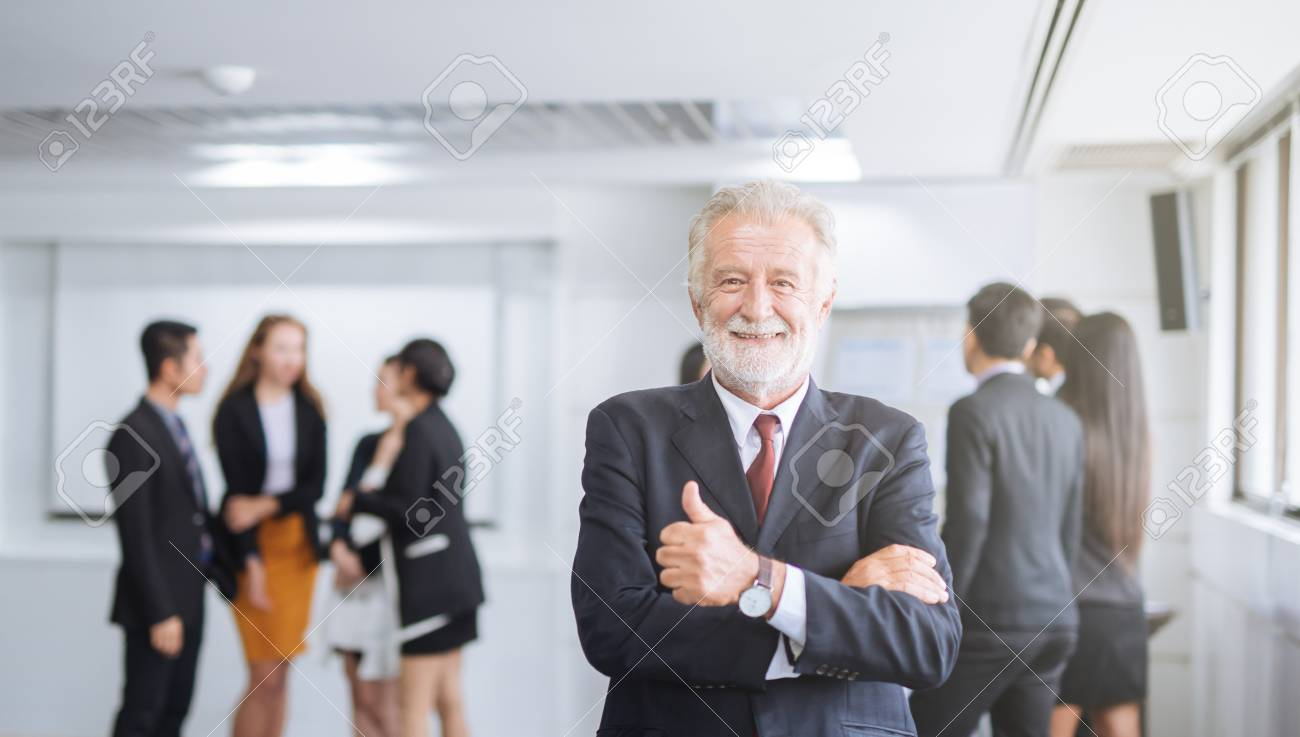 Happy businessman on the background of business team showing thumbs up - 115540855
