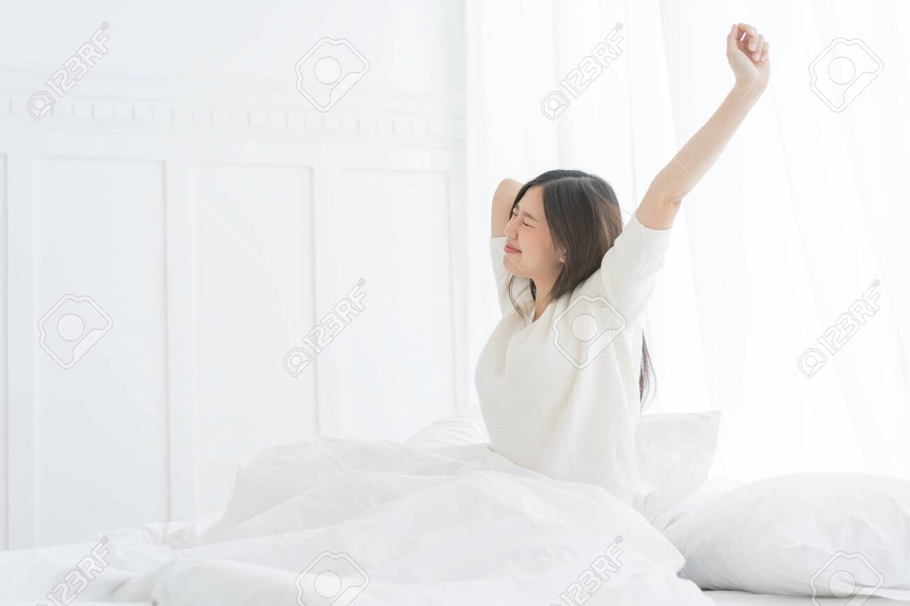 Young Asian woman in the morning she stretching in her bed in the bedroom - 135366342