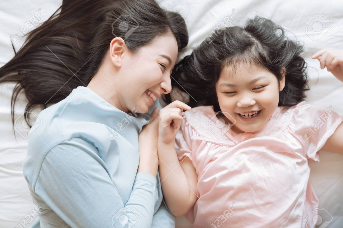 Mother and her daughter child girl hugging her mom in the bedroom .Happy Asian family - 135371162