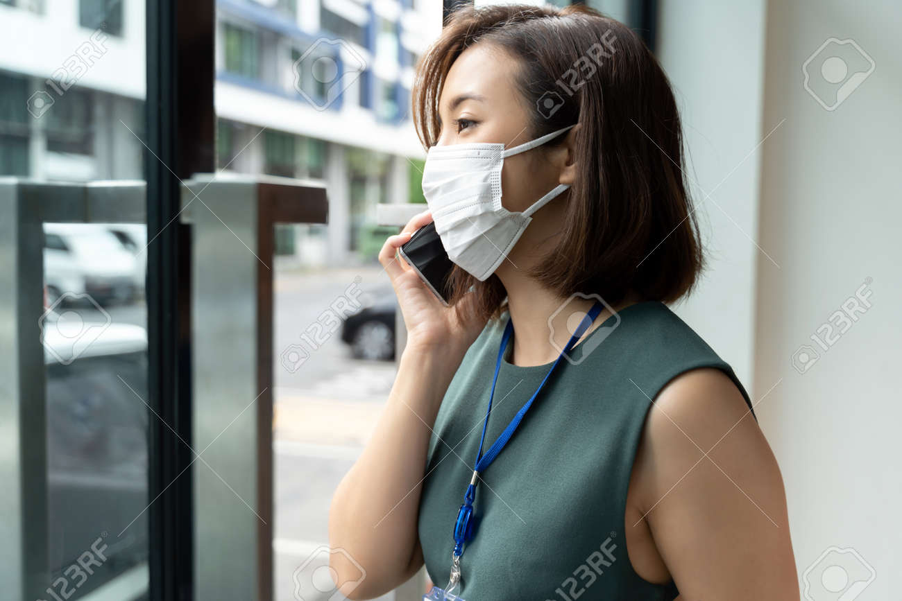 Portrait Asian business woman wearing hygienic mask talking on the phone outside office. - 162245012