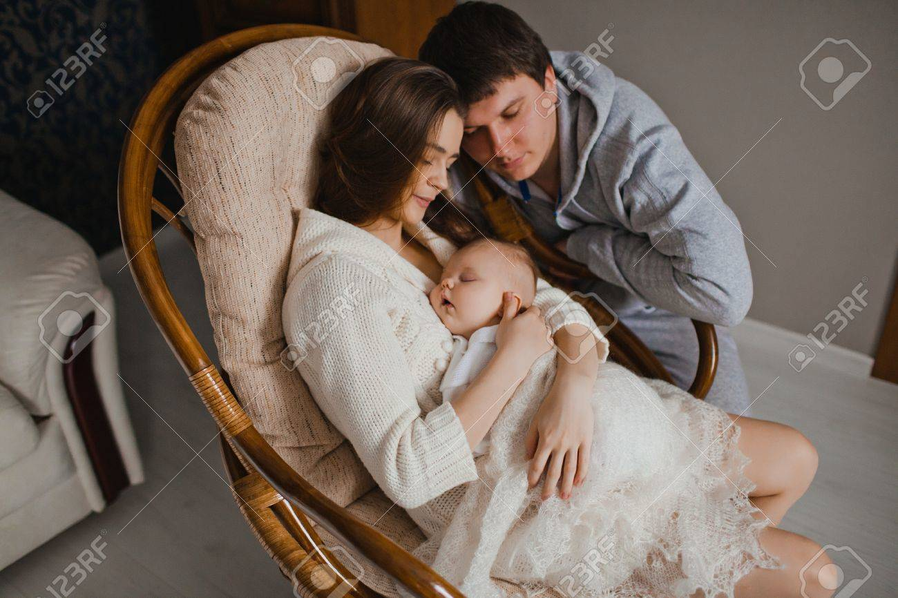 young mother and father holding her newborn baby in their apartment Stock Photo - 17412667