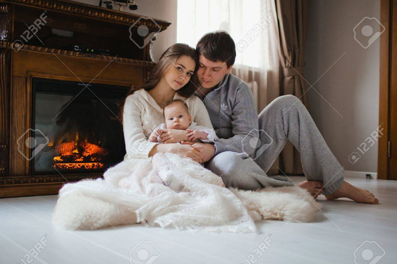 young happy family sitting on floor near fireplace in their apartment Stock Photo - 17412730