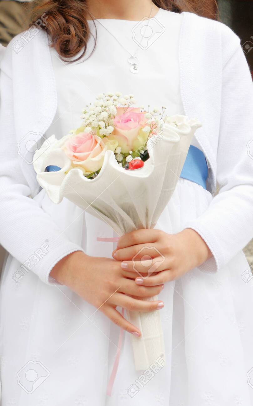 Young girl holding first communion flower bouquet in her hands - 126369007