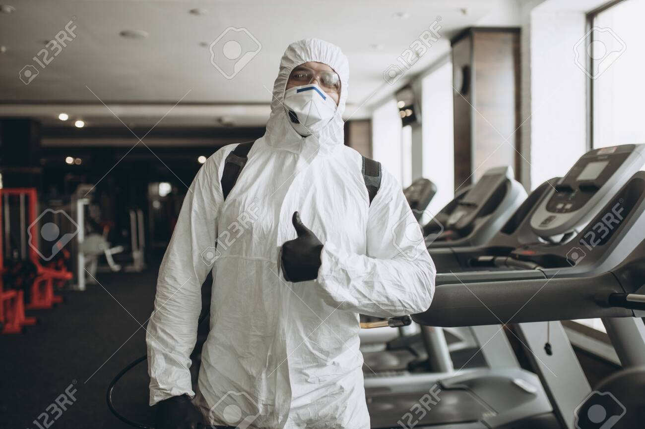 Cleaning and Disinfection in crowded places amid the coronavirus epidemic Gym cleaning and disinfection Infection prevention and control of epidemic. Protective suit and mask and spray bag - 143780933