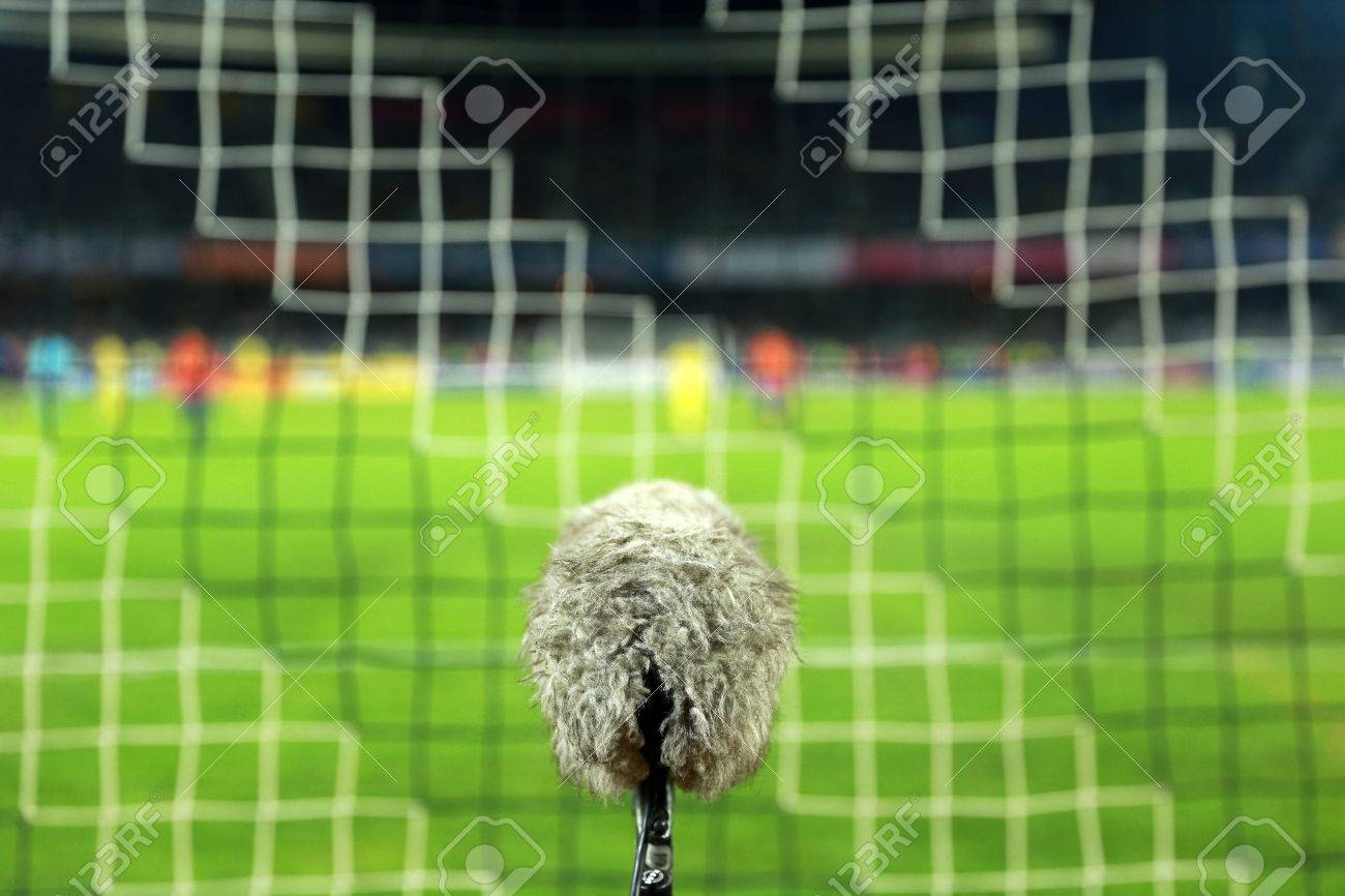 9ea6fab6c Big and furry sport microphone on a soccer field behind the goal net Stock  Photo -