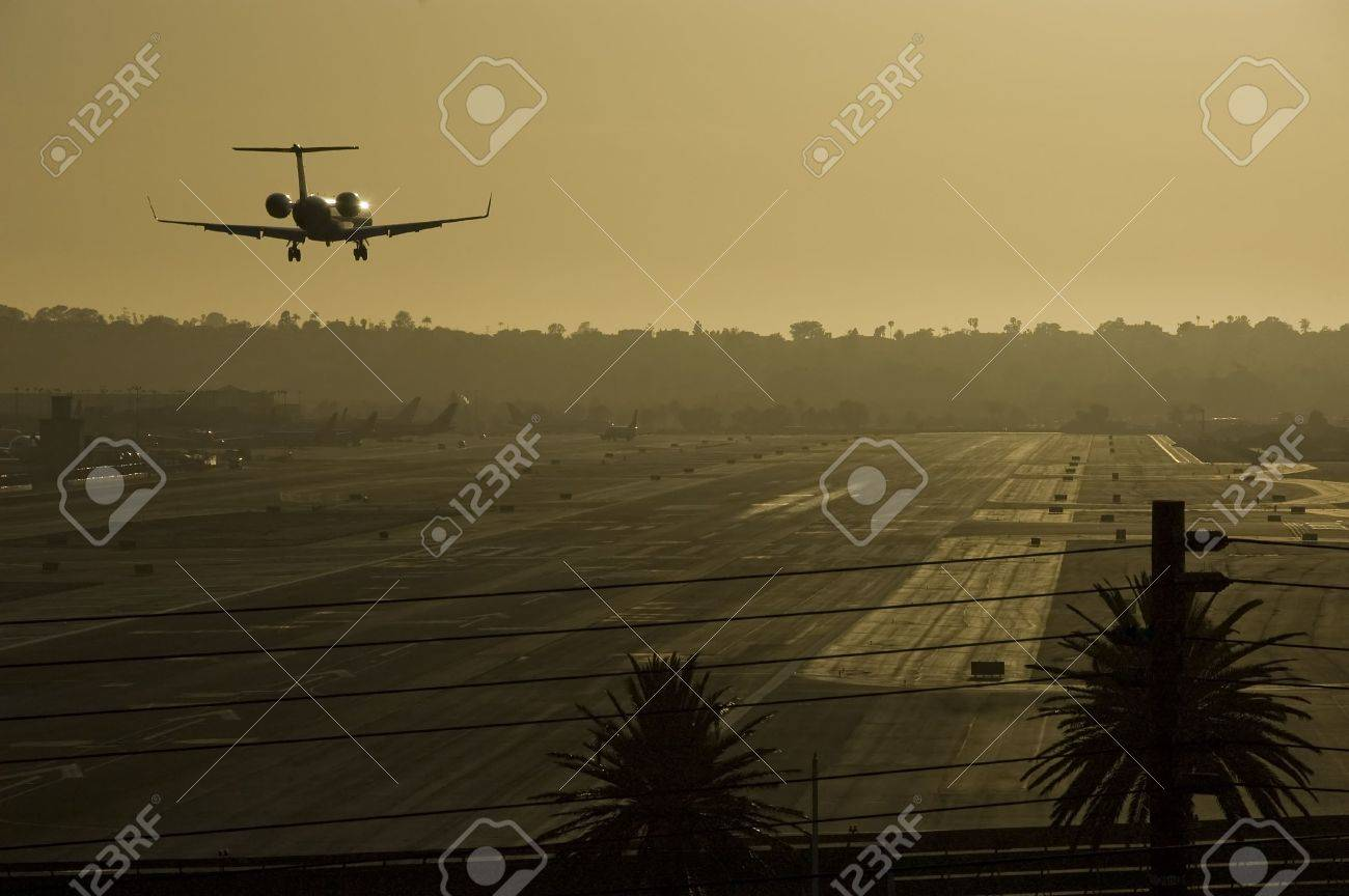 Small jet is about to land on runway. Sunset light gives a gold cast to the entire image. San Diego Airport, California,USA. Stock Photo - 6187497