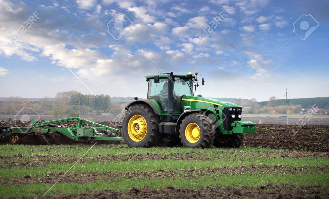 agricultural work plowing land on a powerful tractor - 17524866