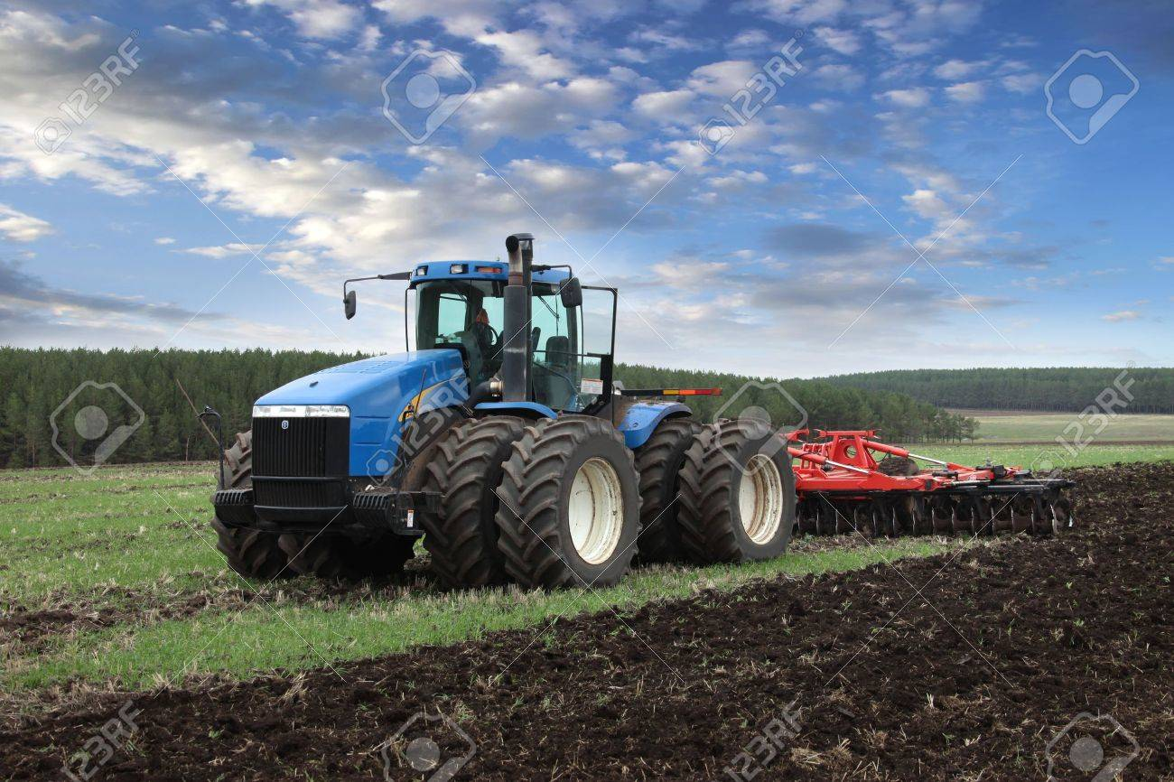 agricultural work plowing land on a powerful tractor - 17524580