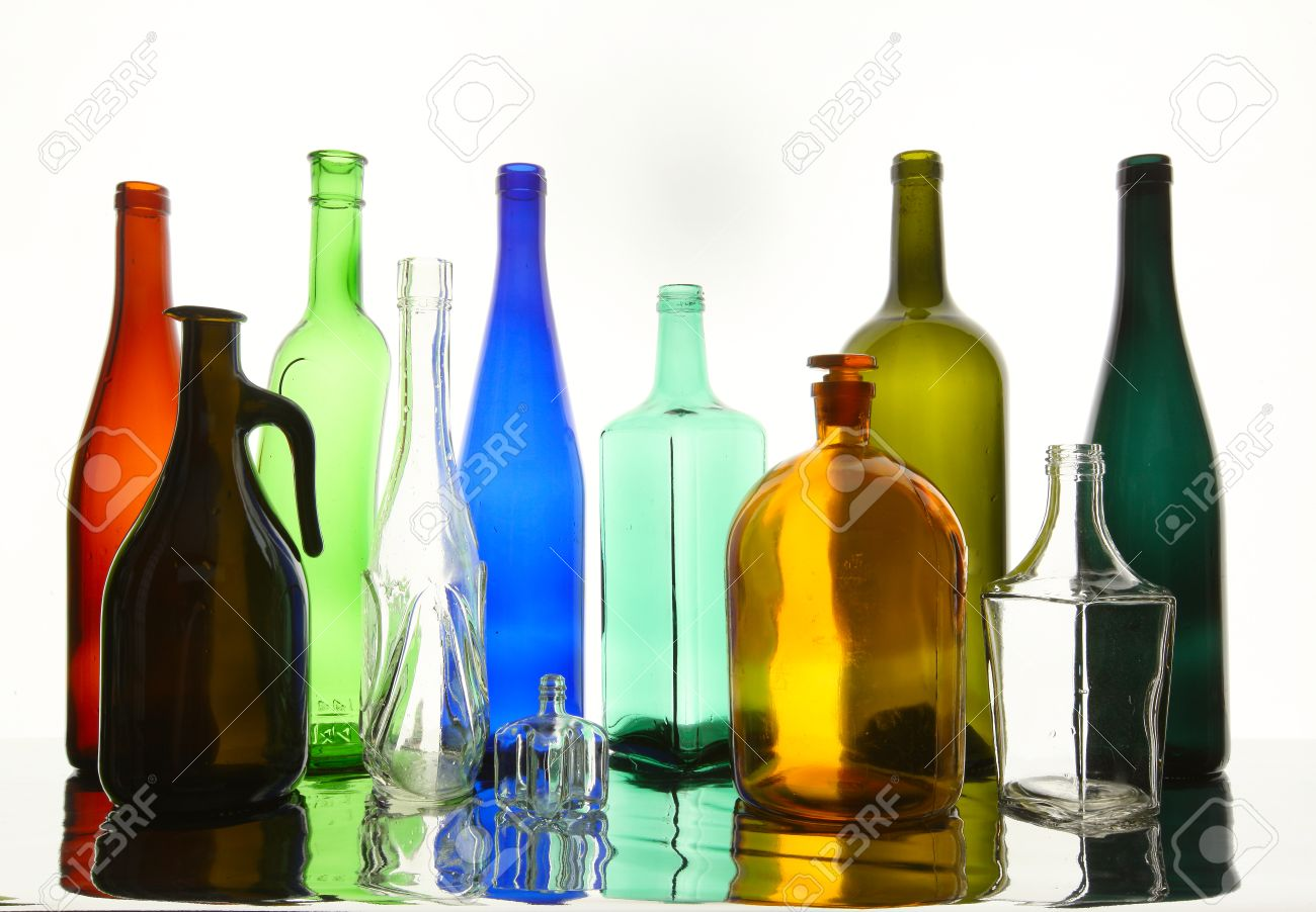close up clean transparent colored glass bottles of different shapes on the mirror surface in - Colored Glass Bottles