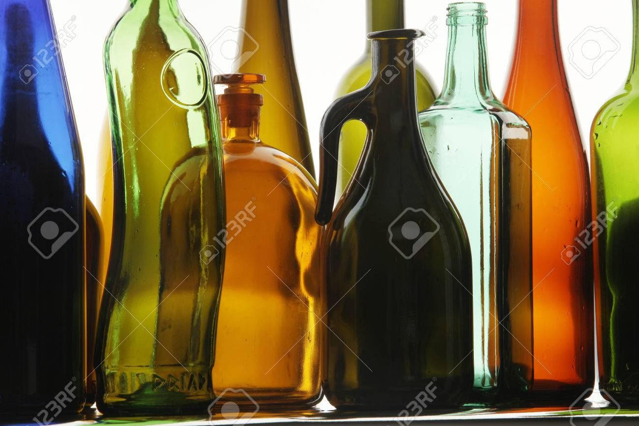 close up clean transparent colored glass bottles of different shapes on the mirror surface in - Colored Glass