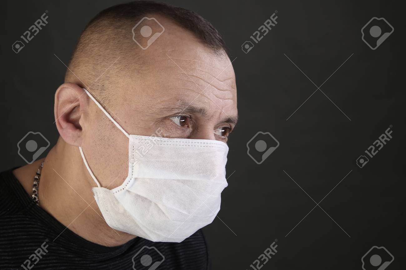 closeup portrait man in a black T-shirt and a medical mask on a gray background studio - 97213654