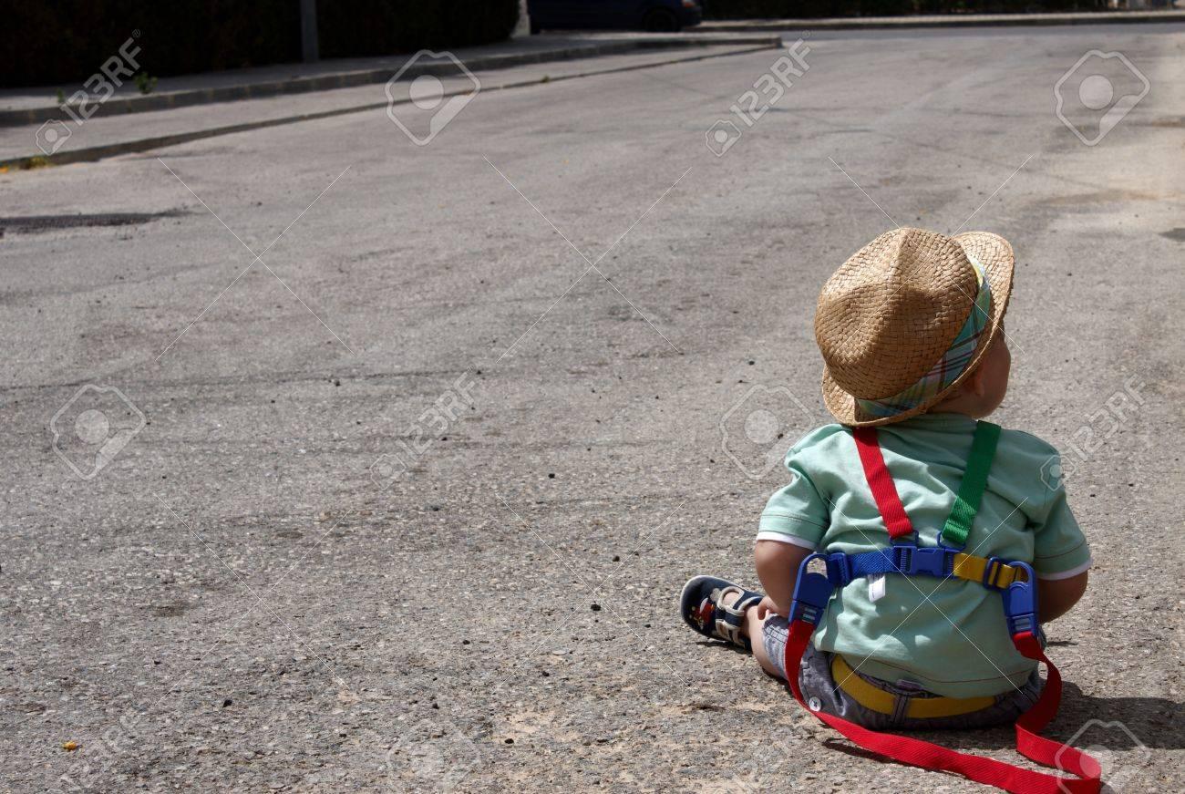 Klettergurt Kind : Ein kind sitzt auf der straße mit dem klettergurt lizenzfreie