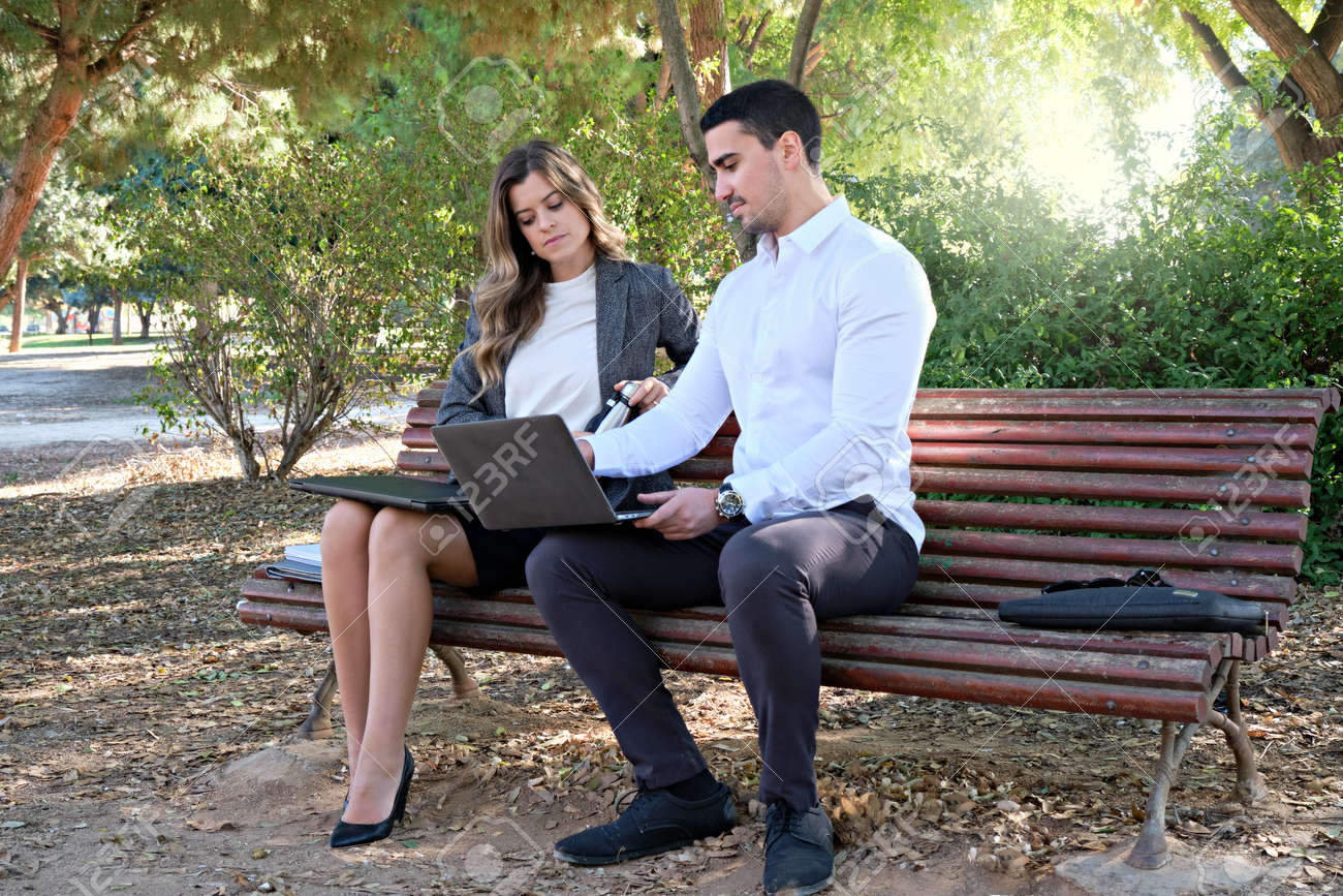 Young businesswoman negotiating with executive man on park bench - 158953783