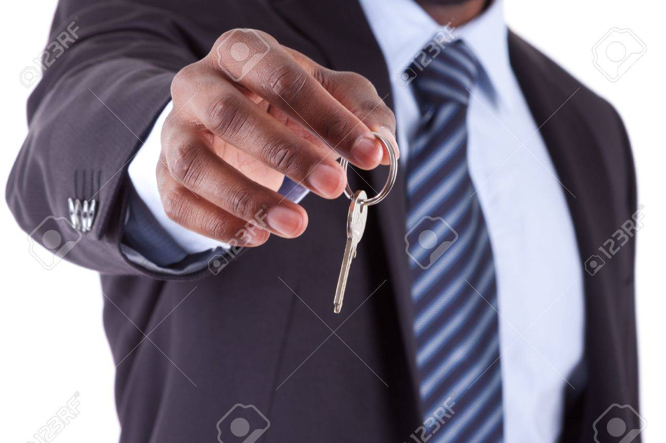 Young African American businessman holding a house key, isolated on white background - 16589209
