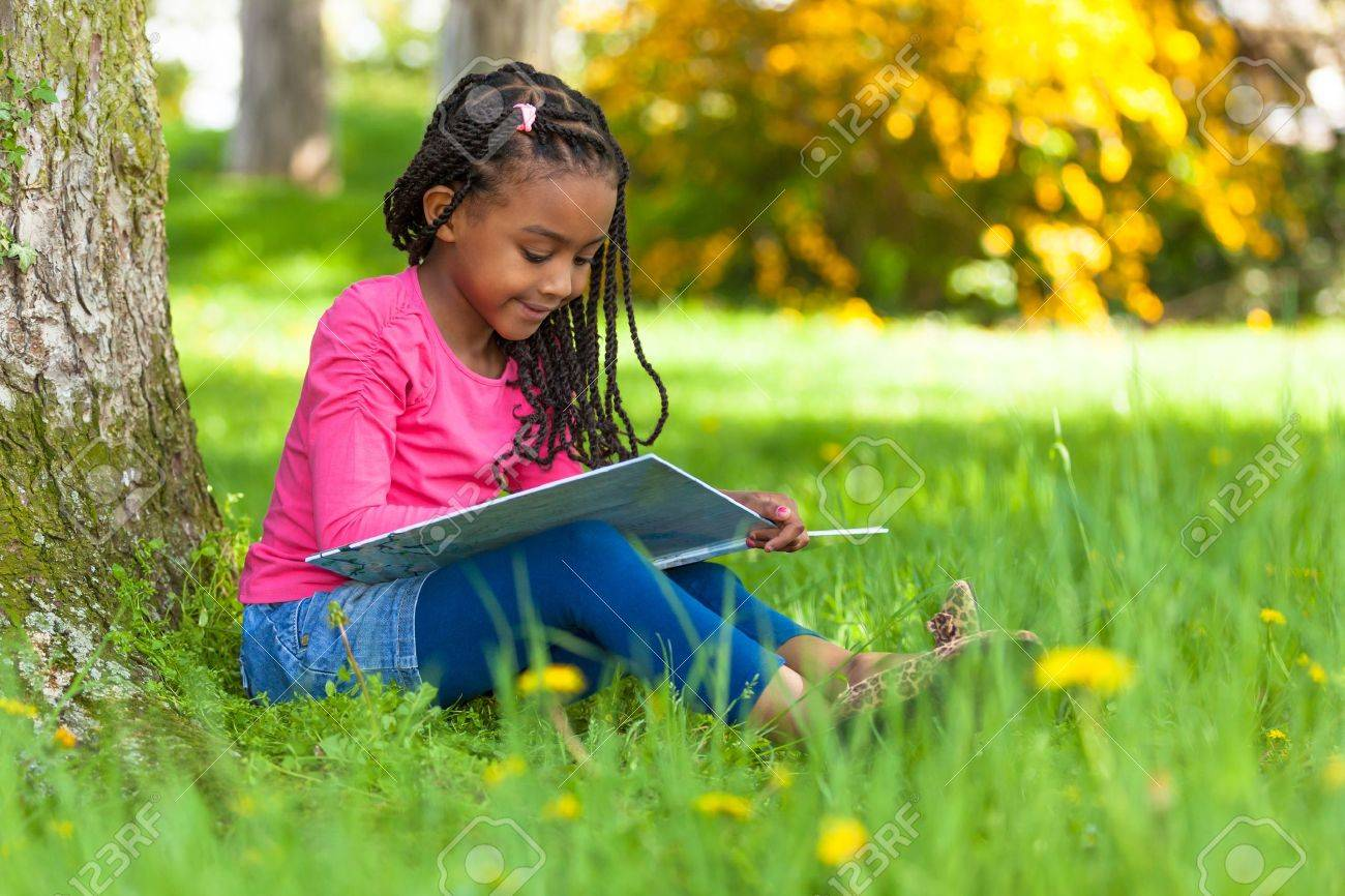Outdoor portrait of a cute young black little  girl reading a book - African people Stock Photo - 19475965