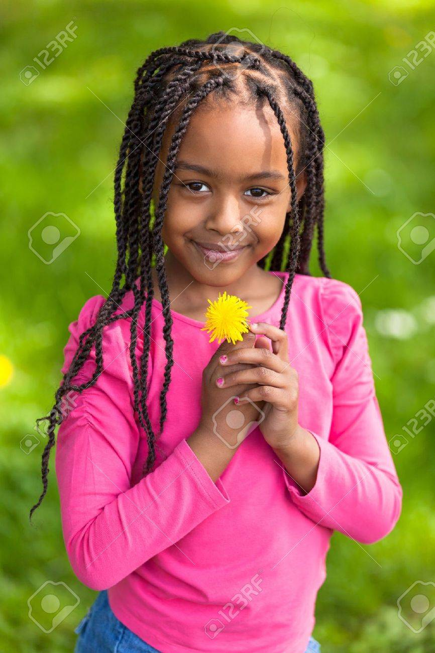 Outdoor Portrait Of A Cute Young Black Girl Holding A Dandelion