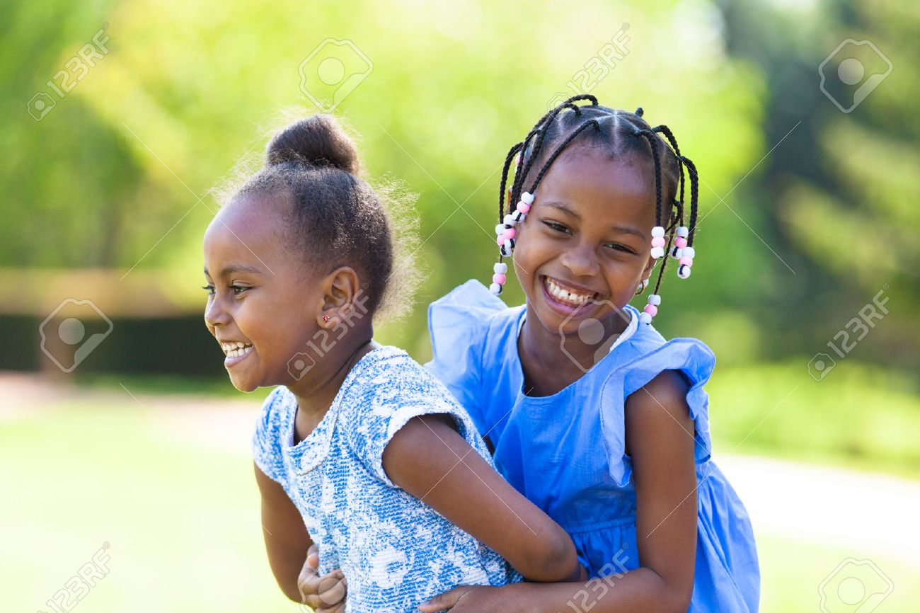 Outdoor portrait of a cute young black sisters laughing - African people - 28379658