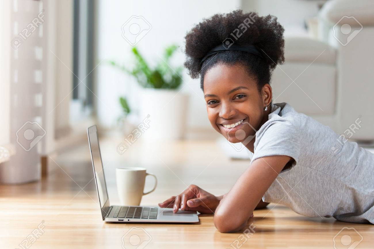 African American woman using a laptop in her living room - Black people Stock Photo - 38633187