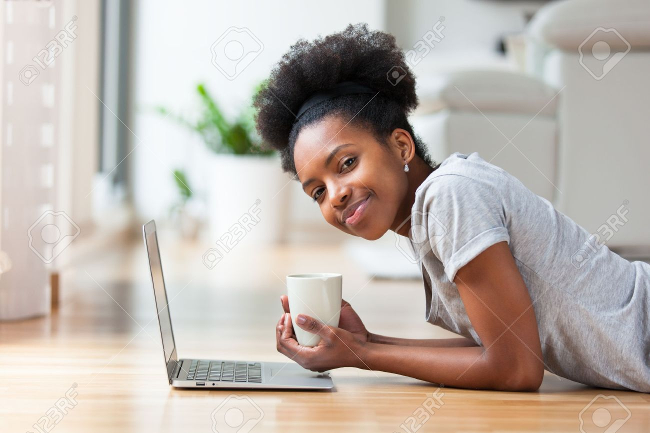 African American woman using a laptop in her living room - Black people Stock Photo - 38633190
