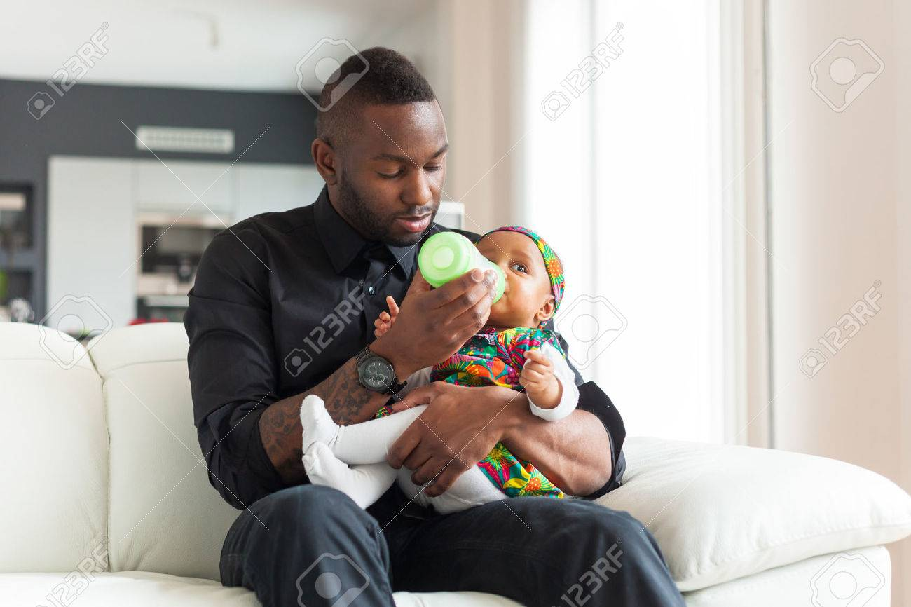 Young african american father giving milk to  her baby girl in a baby bottle Stock Photo - 38705630
