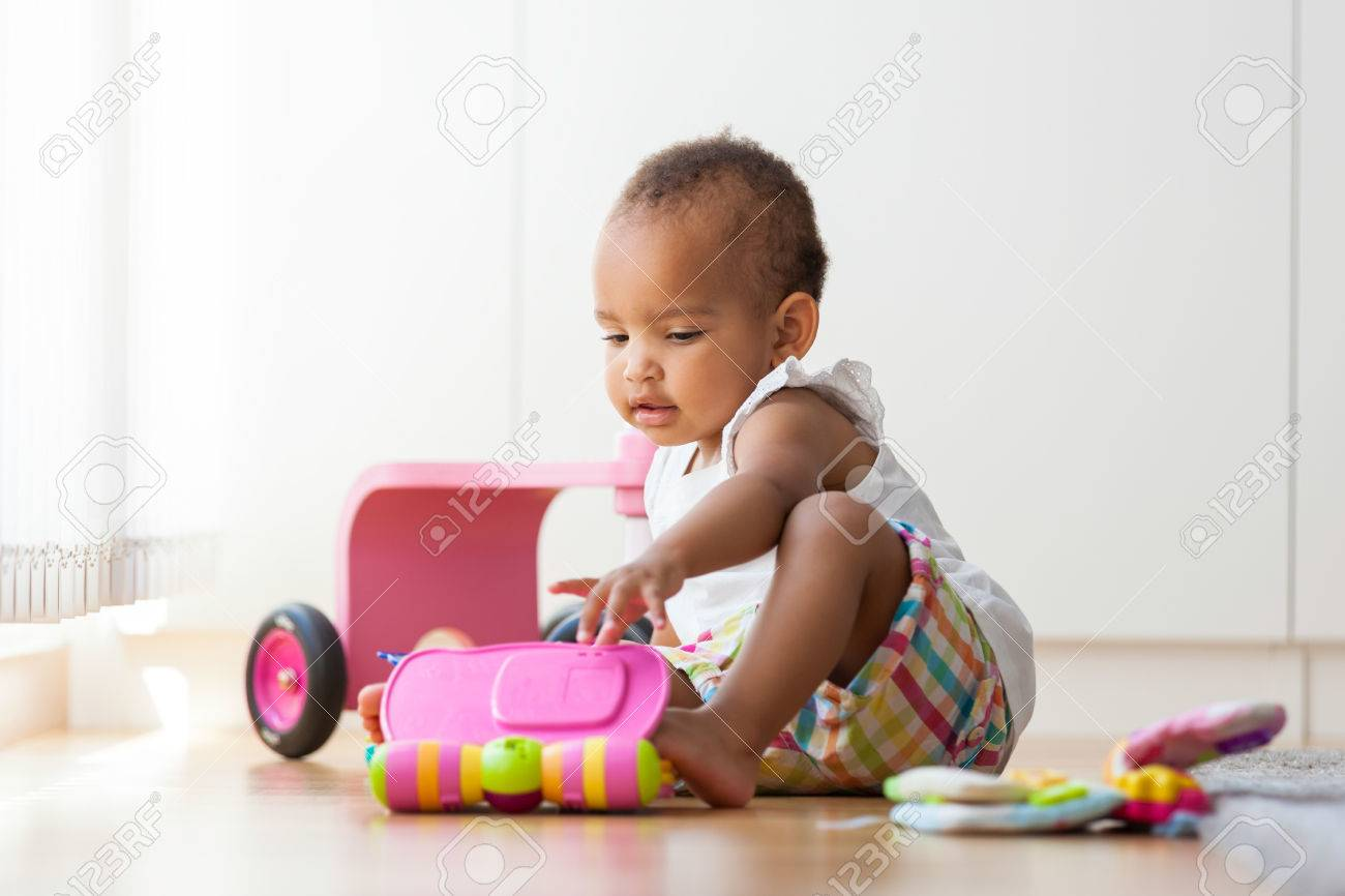 Portrait of little African American little girl sitting on the floor and playing  - Black people Stock Photo - 43217919