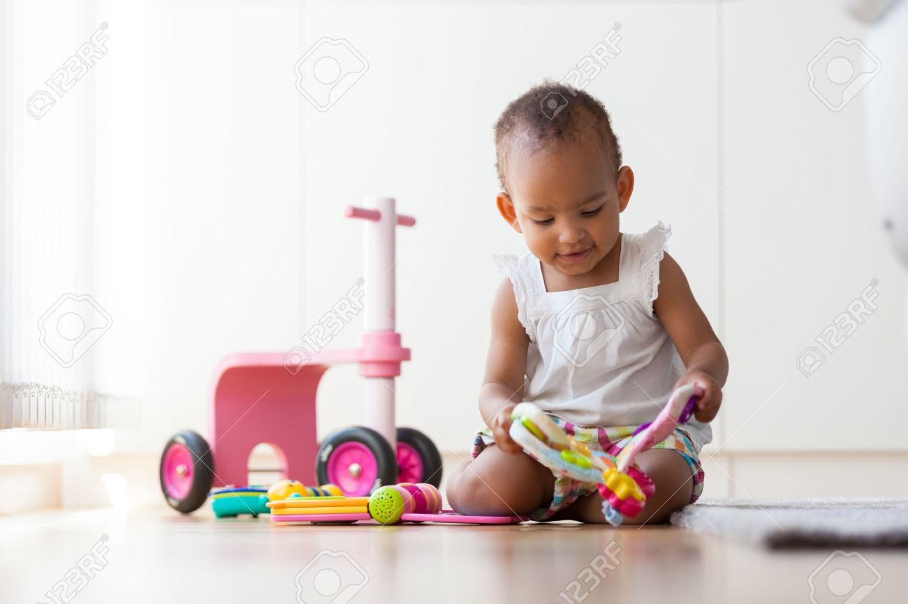 Portrait of little African American little girl sitting on the floor and playing  - Black people Stock Photo - 43224326