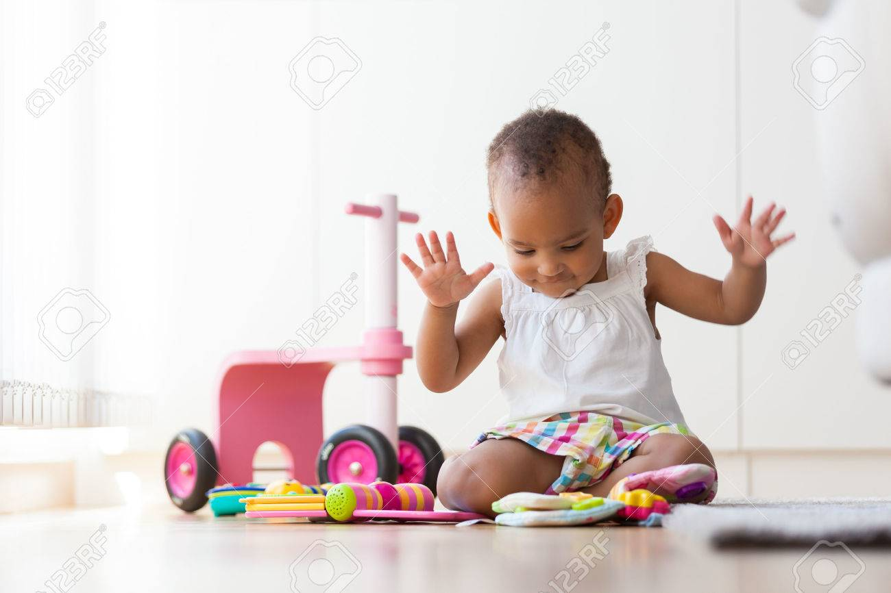 Portrait of little African American little girl sitting on the floor and playing - Black people - 43224720