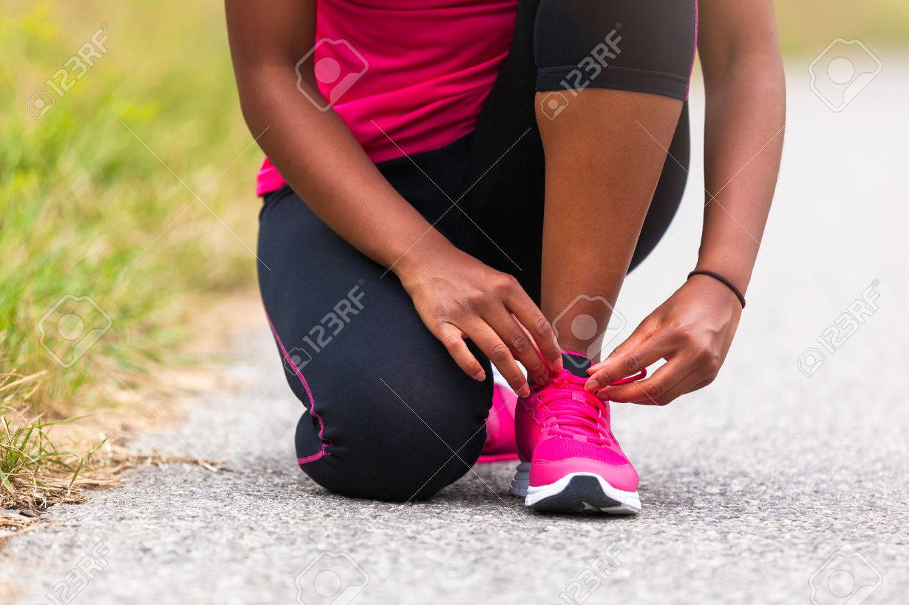 African american woman runner tightening shoe lace - Fitness, people and healthy lifestyle Stock Photo - 43561489