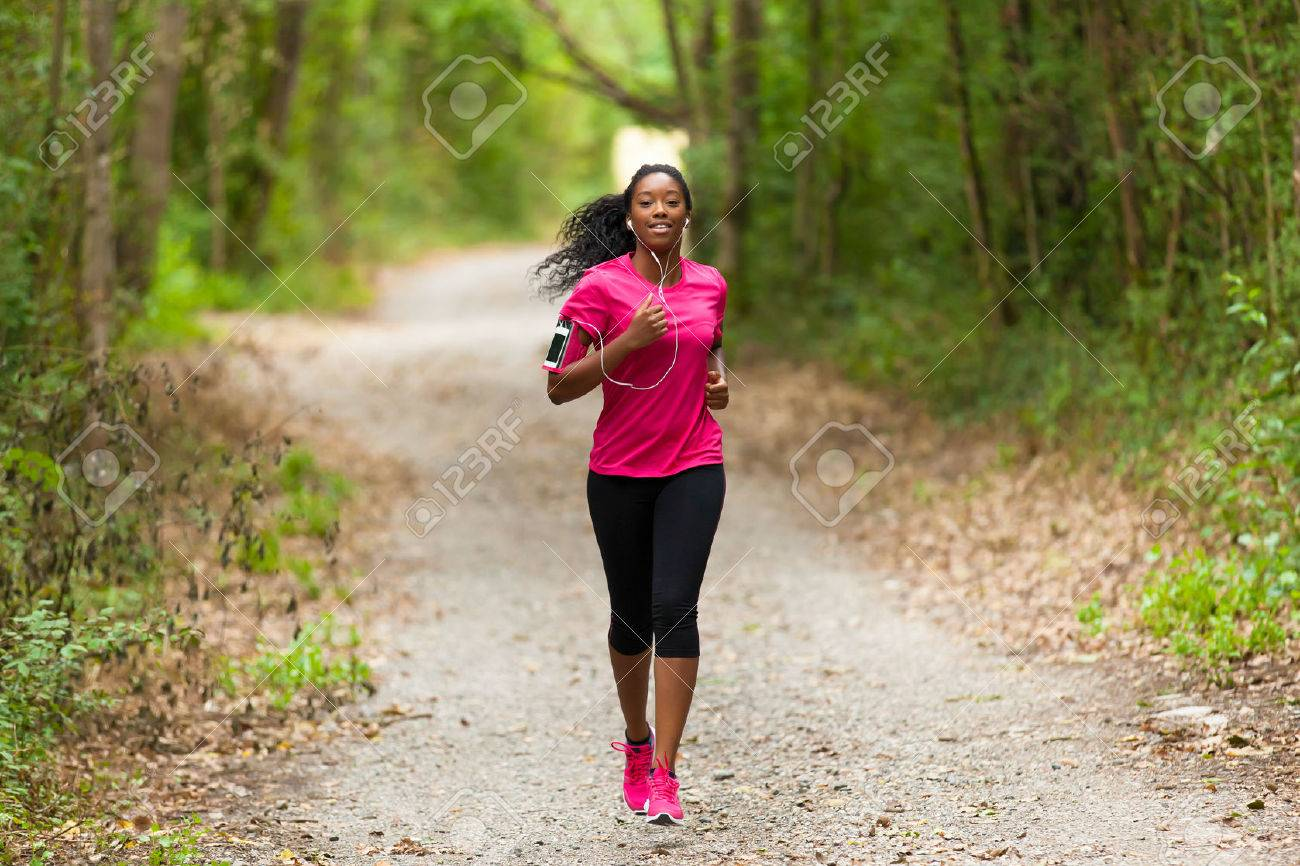 African american woman runner jogging outdoors - Fitness, people and healthy lifestyle - 43561648