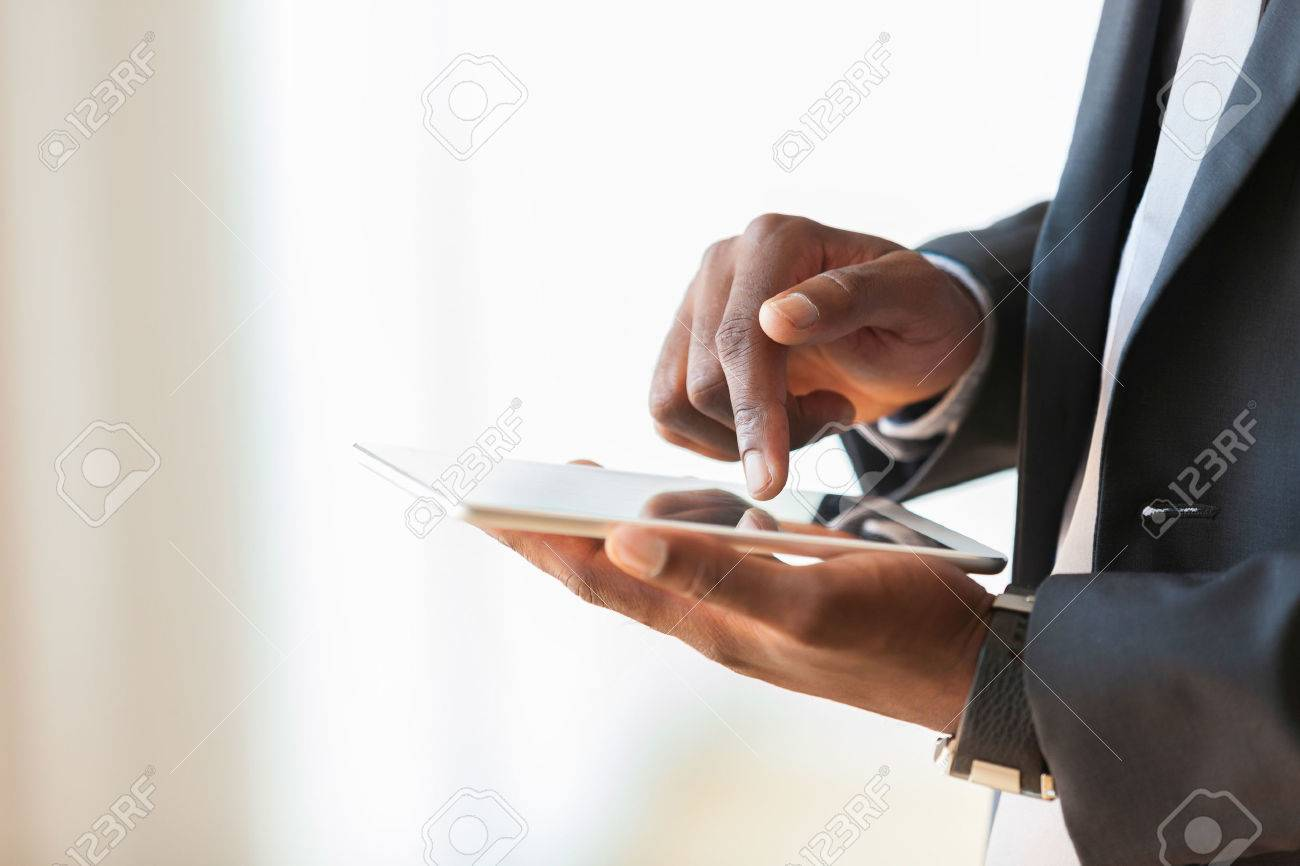 African american business man using a tactile tablet over white background - Black people - 43729015