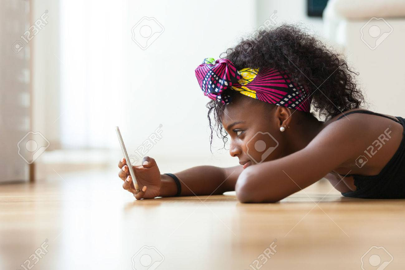 African American woman sending a text message on a mobile phone - Black people Stock Photo - 46714026