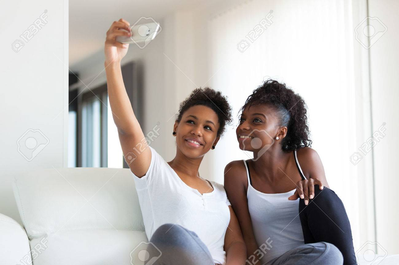 African American teenage girls taking a selfie picture with a smartphone - 46714035