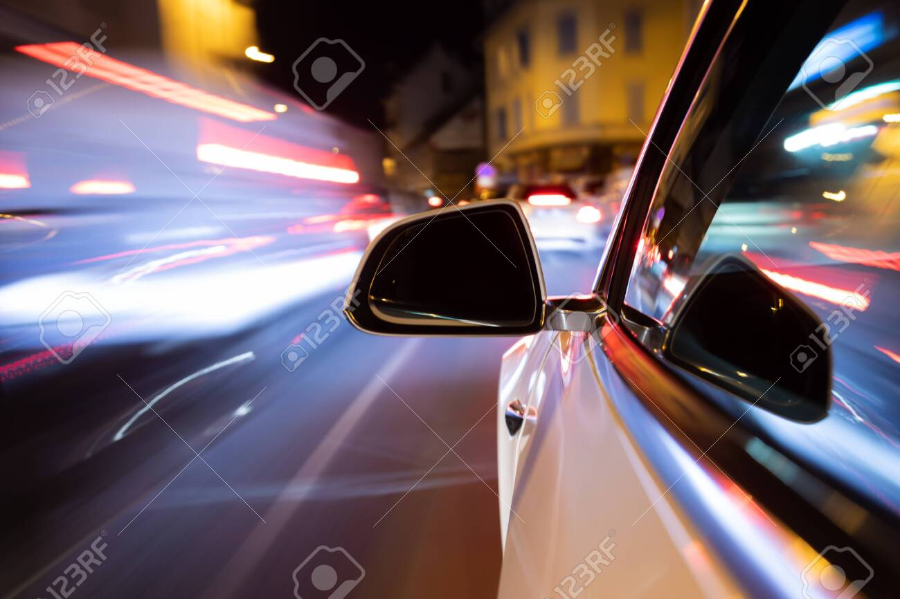 Car light trail while driving in the coty by night - 141208244