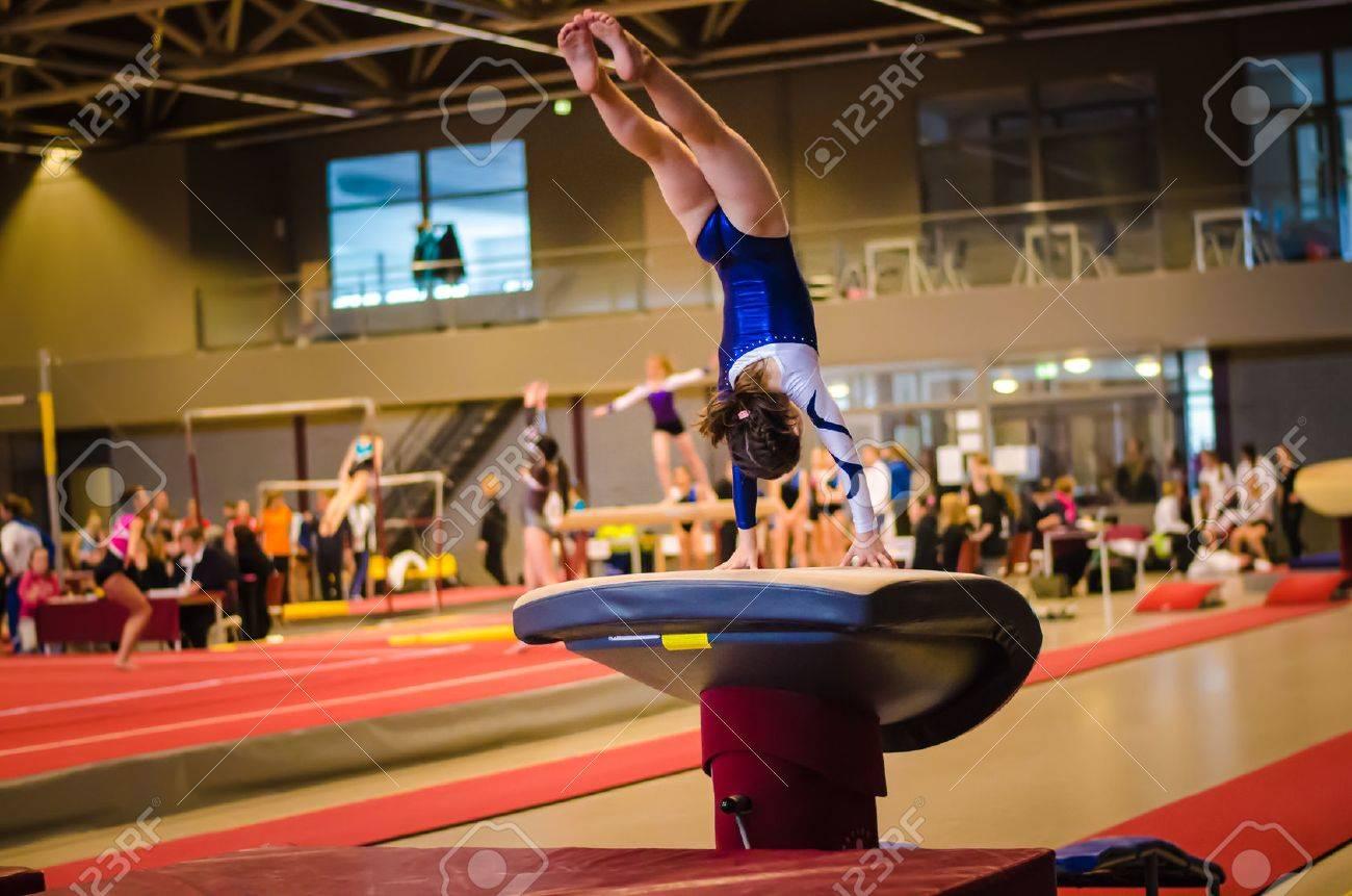 Jeune fille de gymnaste effectuant saut sur une voûte en pratiquant pour le concours Banque d'images - 32500515