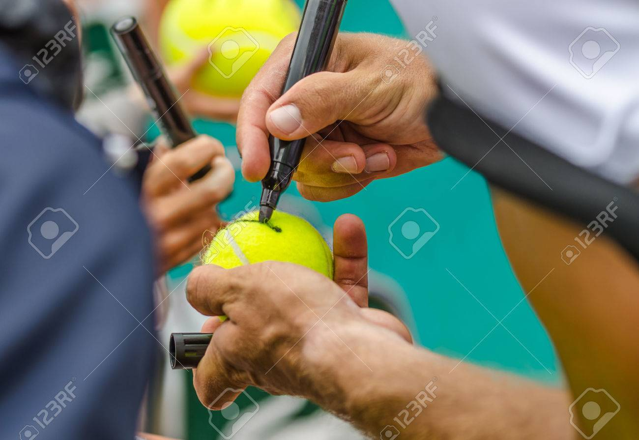 Tennis player signs autograph on a tennis ball after win, closeup photo showing tennis ball and hands of a man making signature, australian open, us open. Banque d'images - 35536324