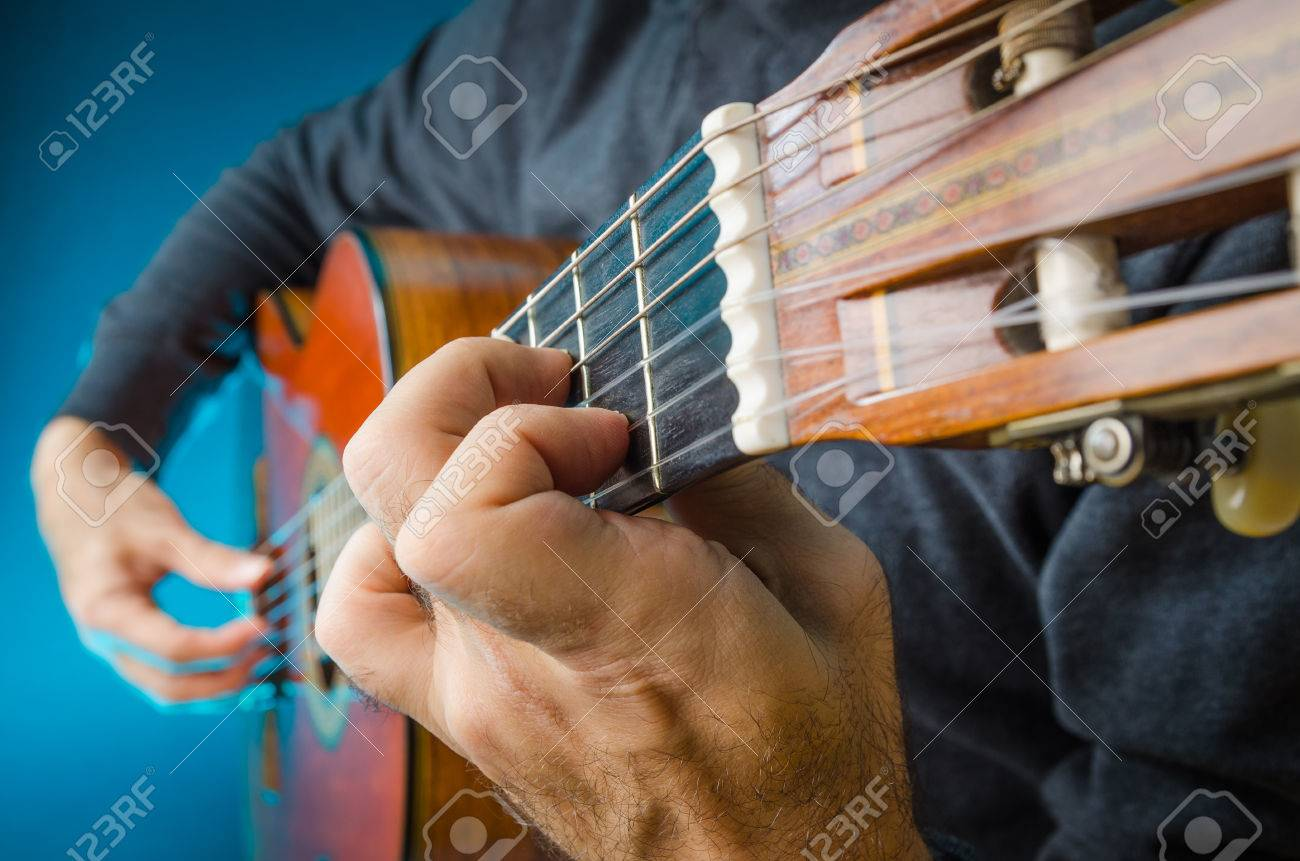 Closeup of a Man playing red classical gutar on concert, with fingers, focus on left hand position. Banque d'images - 35536855