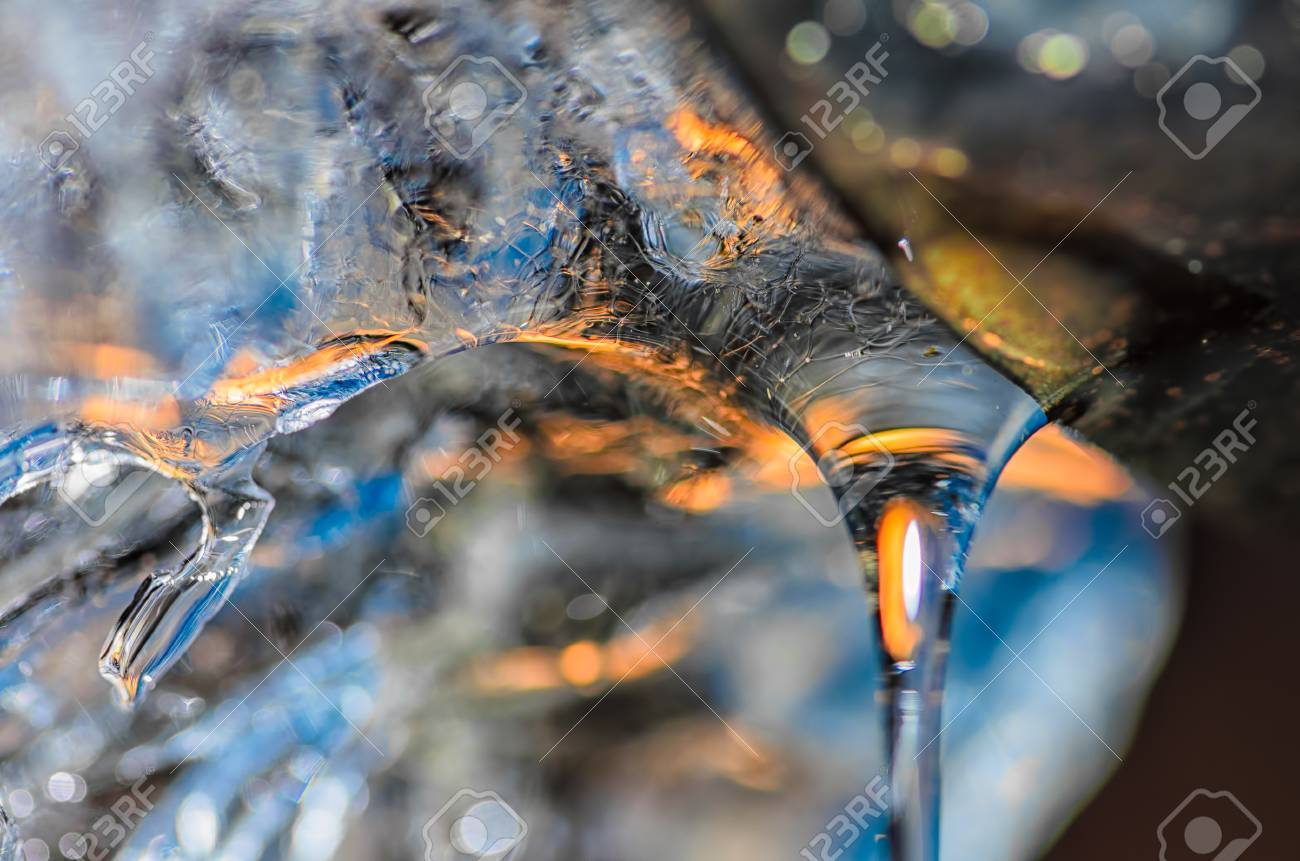 Drop of melting ice water at the drainpipe, with reflections of blue sky and yellow sun rays passing through. Macro with ice structure seen through the drop of water. Banque d'images - 40326117