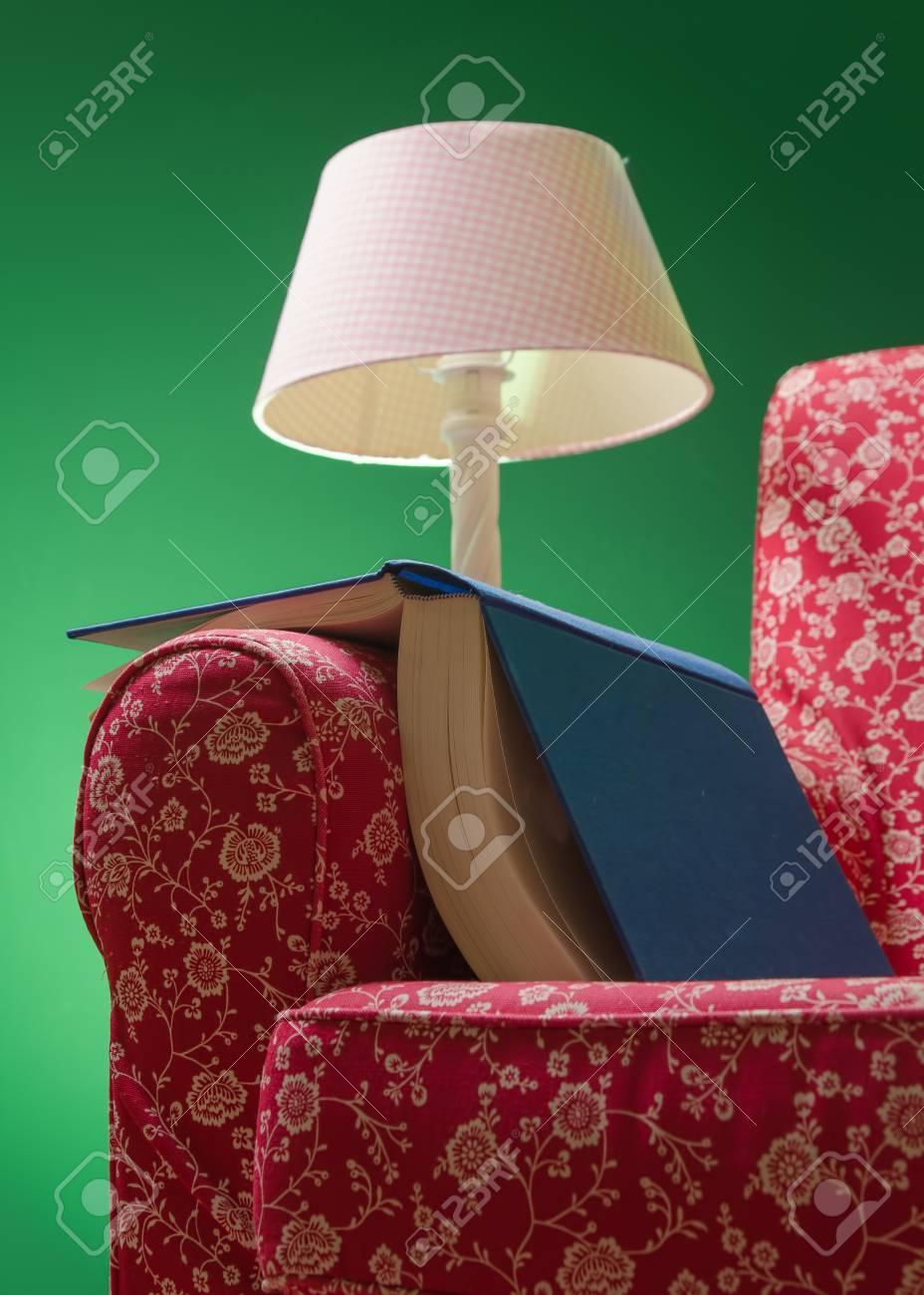 Livre sur le repos du fauteuil rouge à gauche après la lecture, avec un fond vert et une lampe rose éclairant la scène. Banque d'images - 85550612