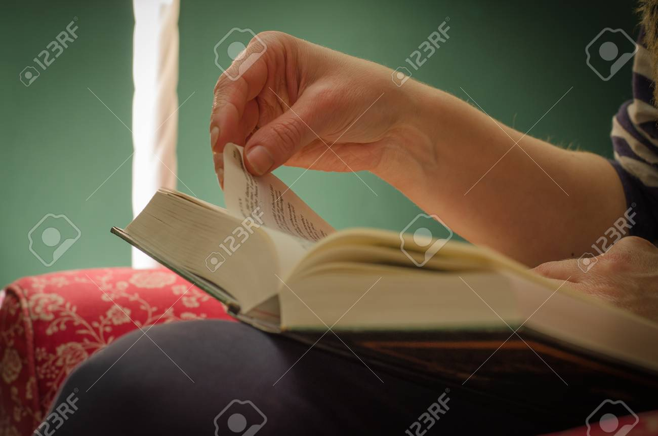 Woman hand folding down a page of a book to mark current page (dog ears), under light of lamp, with green background. Banque d'images - 85549221