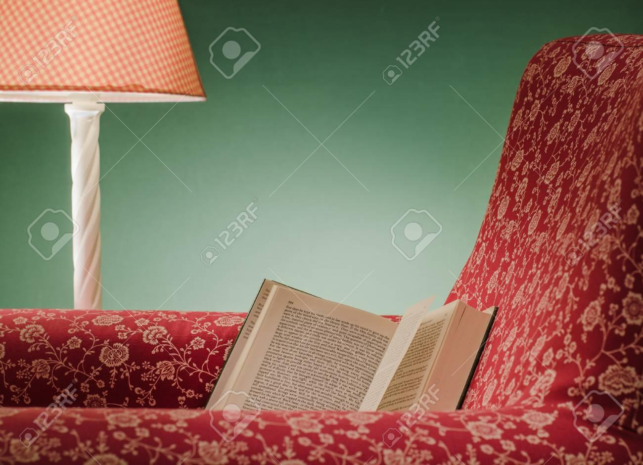 Livre ouvert sur le repos du fauteuil rouge à gauche après lecture, avec fond vert et lampe rose. Banque d'images - 85657390