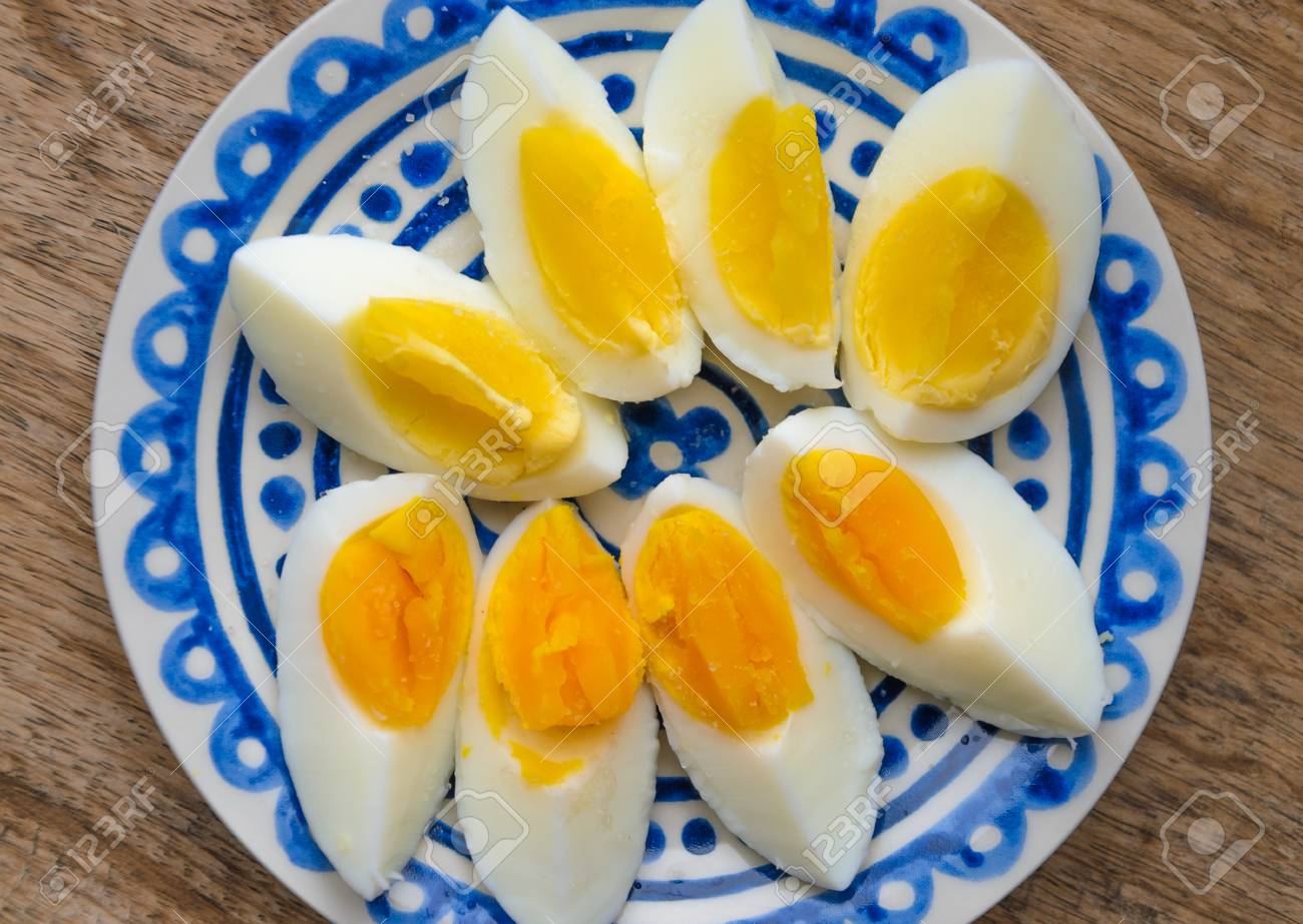 Two colors yolk, sliced hard boiled eggs in a blue decorated plate on wooden kitchen table. One egg yolk with yellow collor, the other one orange. Banque d'images - 86674016