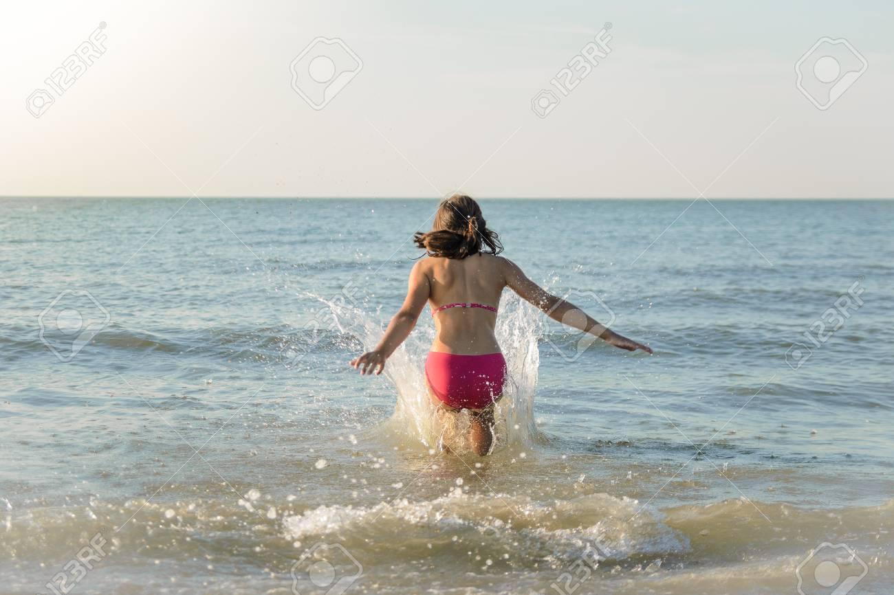 Petite jolie fille courant vers la mer, sautant dans l'eau. Plage ensoleillée dans la mer du Nord. Banque d'images - 86955305