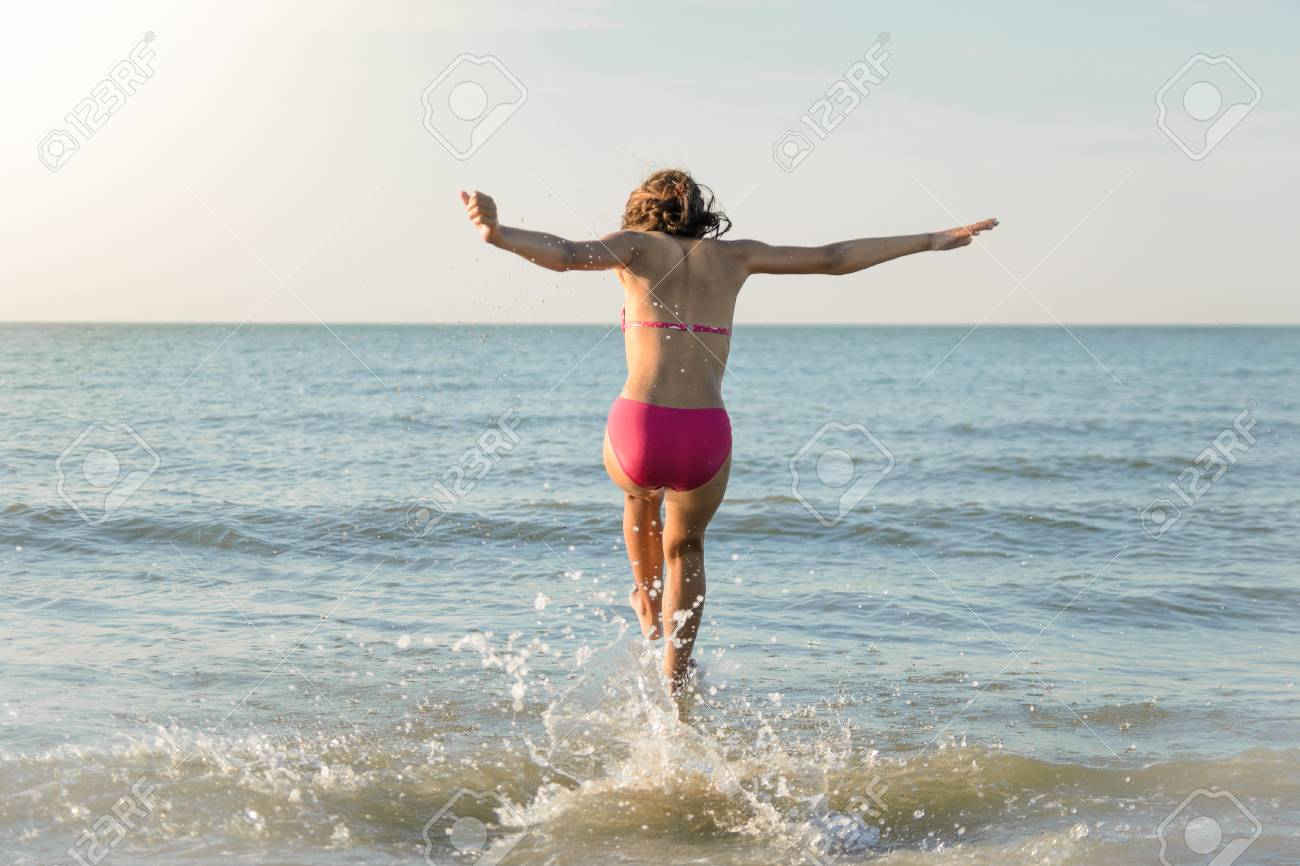 Little pretty girl running to the sea, jumping in the water. Sunny beach in the nord sea. Banque d'images - 86955306
