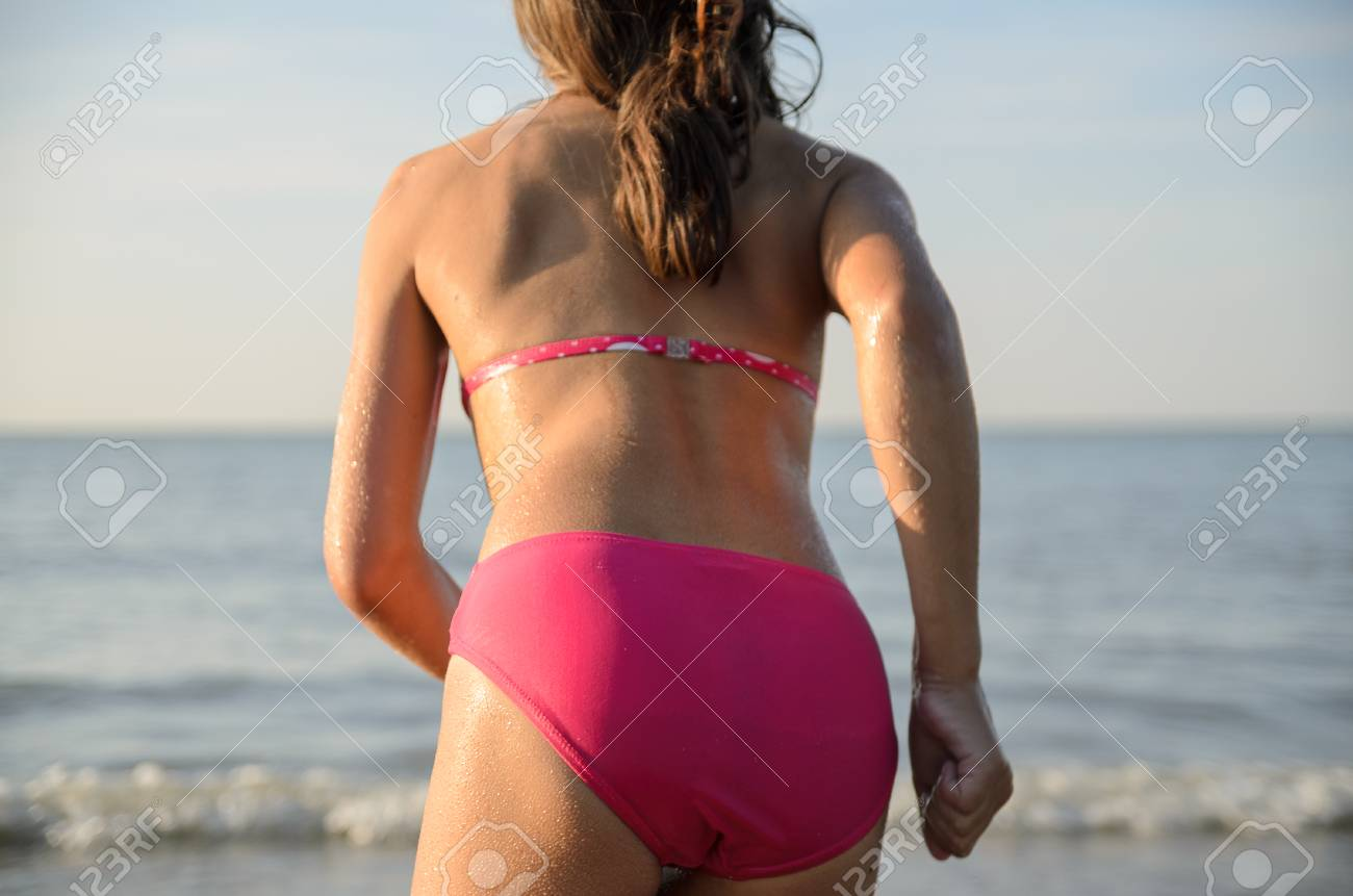 Little pretty girl running to the sea, jumping in the water. Sunny beach in the nord sea. Banque d'images - 87155256