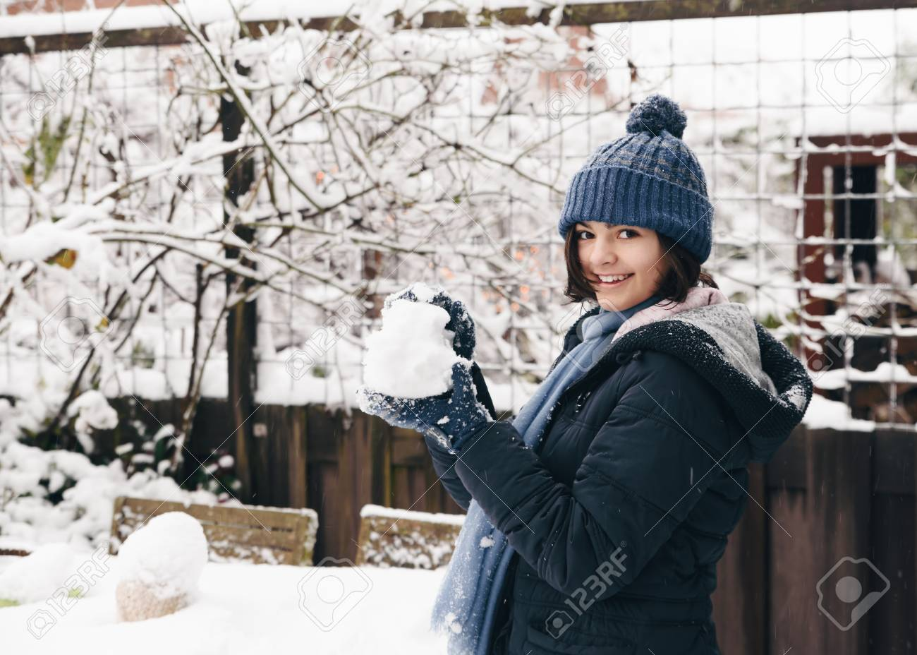 Little girl makes snowballs in a backyard, enjoying the first snow in late autumn. Banque d'images - 95408061