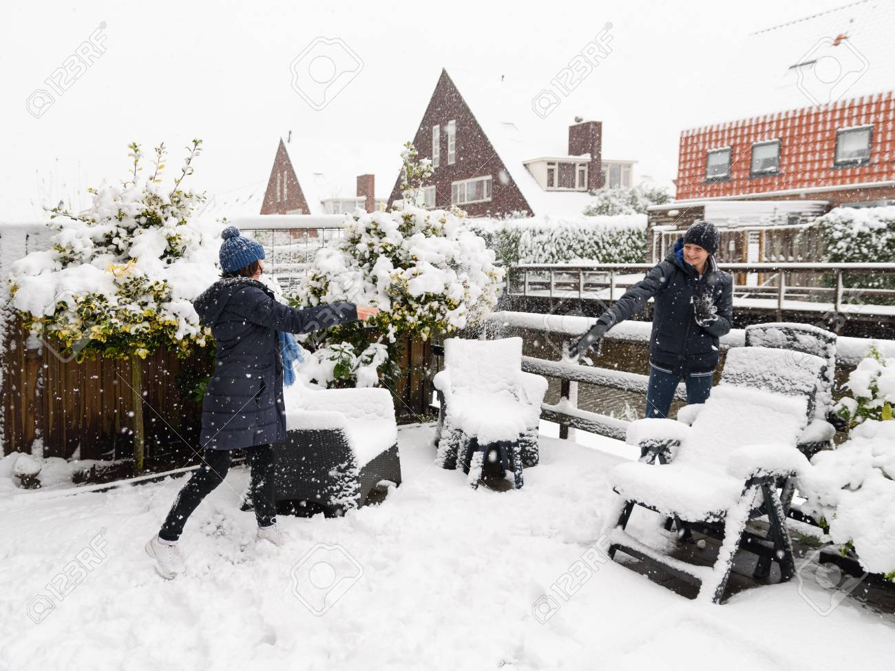 Two kids, children, playing snowballs in a backyard, first snow in late autumn. Banque d'images - 95408062