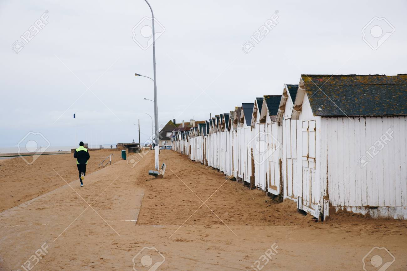 Runner and white bathing beach houses, cabins in a row on the beach Banque d'images - 95286628