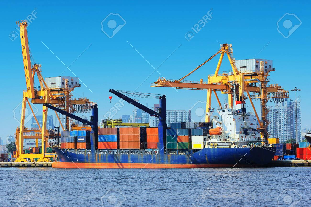 Container Cargo freight ship with working crane bridge in shipyard. - 123288644