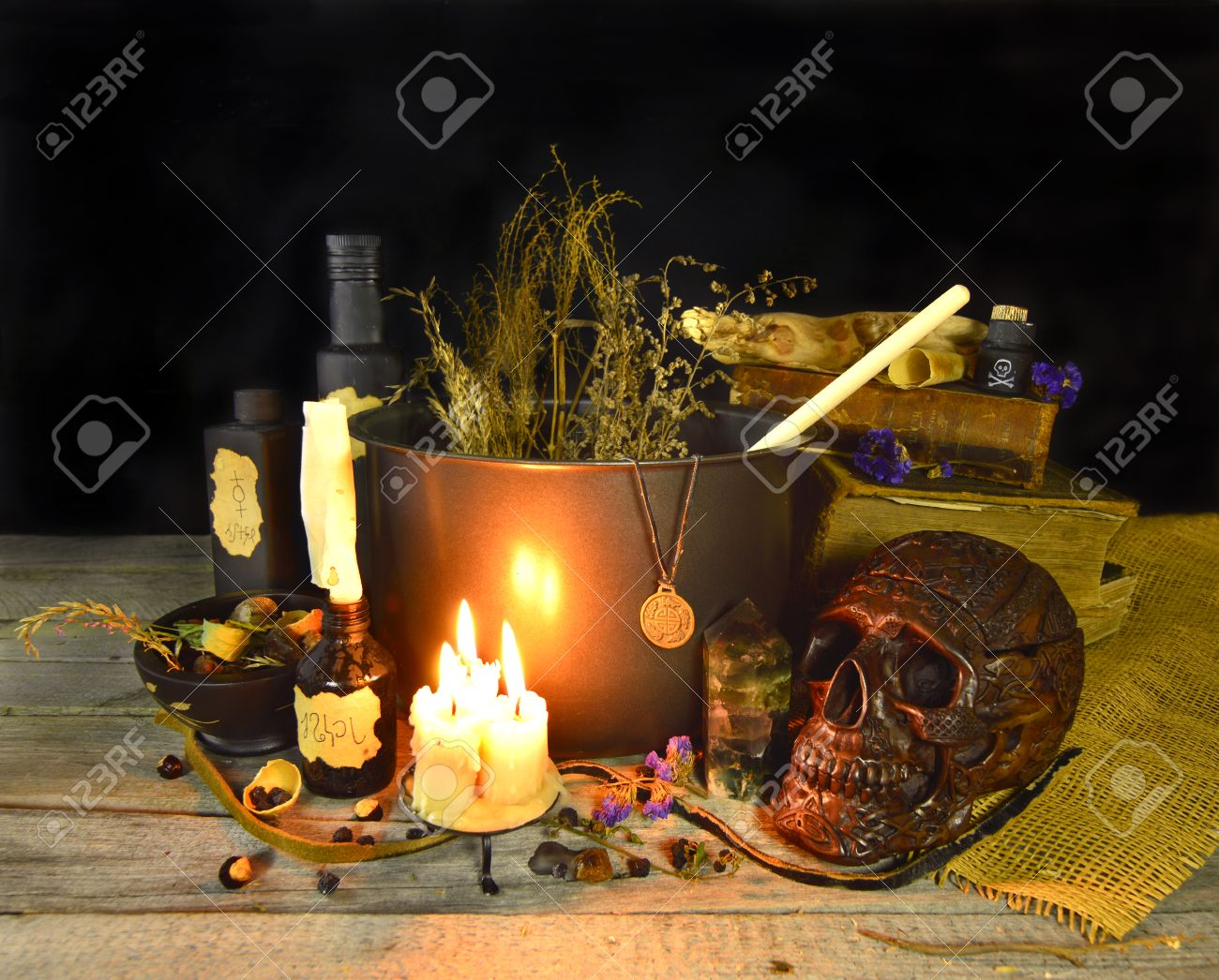 Halloween still life with witch cauldron, burning candles and