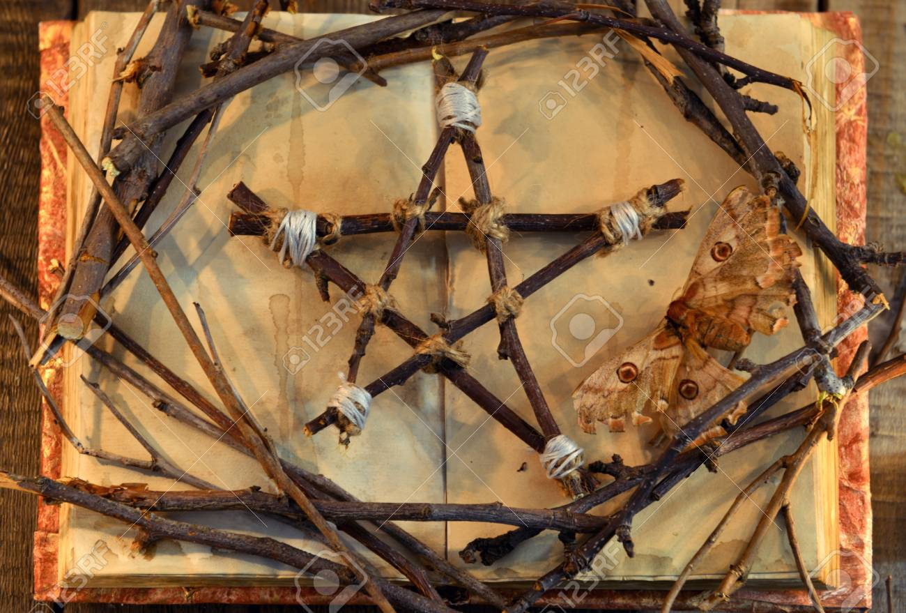 Stock Photo - Wicca pentagram, moth - death symbol, and tree branches on  open book with shabby pages in candle light, top view. Occult, esoteric,  divination ...